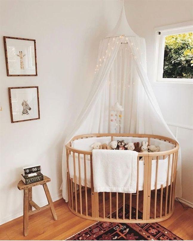 nursery, white wall, wooden round crib, white curtain,
