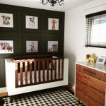 Nursery, Wooden Floor, Black White Plaid Rug, Wooden Crib, White Covered, White Wall, Dark Green Accent Wall, Wooden Cabinet White Top