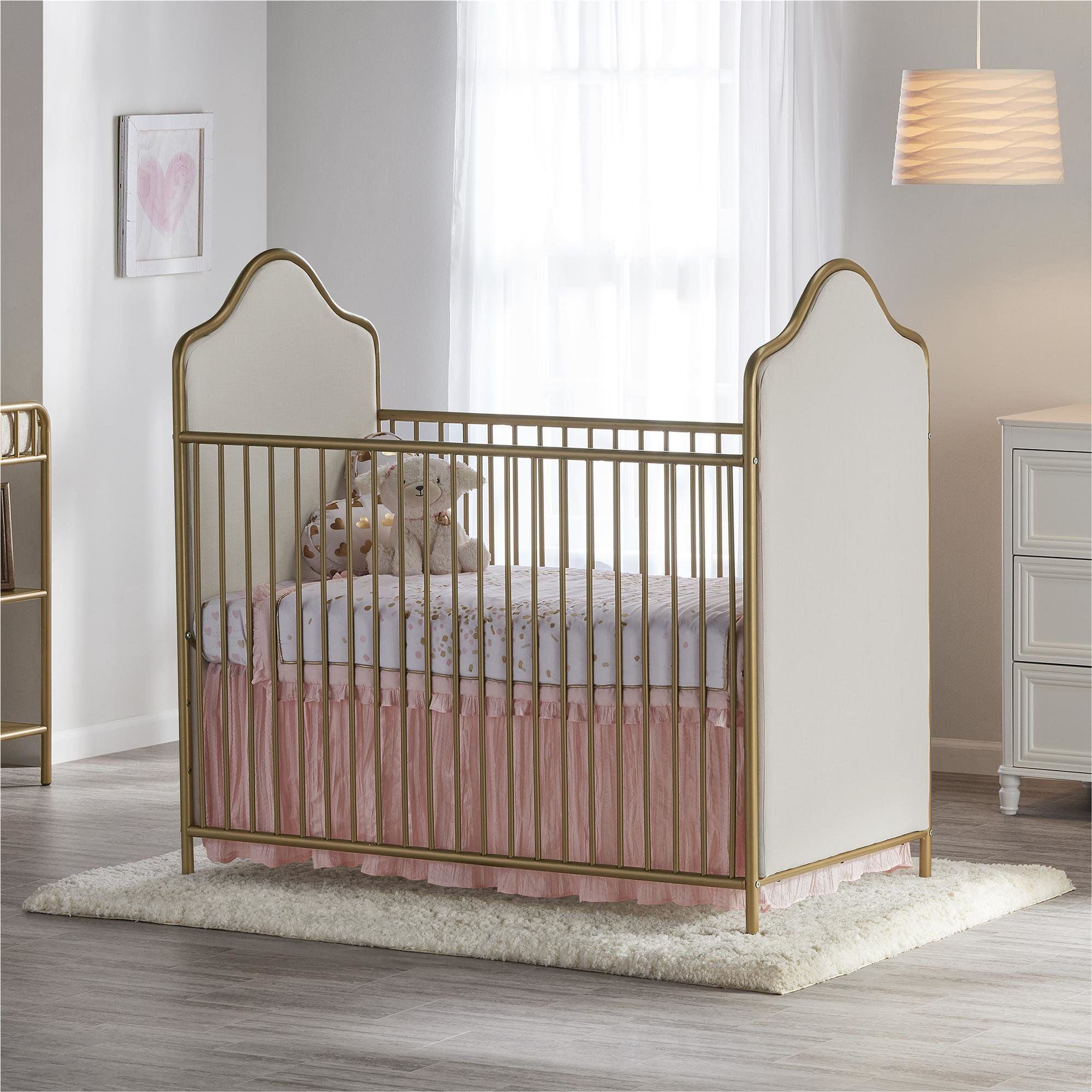 nursery, wooden floor, crib with golden fences, white headboard, white wall, white rug