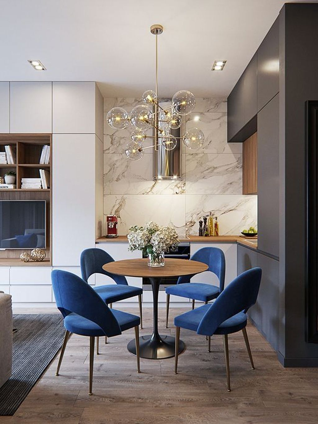 open kitchen, wooden floor, grey cabinet, white marble wall, white cabinet, grey rug, wooden round table, blue chairs, glass chandelier