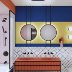 Orange Vanity Table, Indented Sink, White Patterned Wall, Blue Yellow Wall, Round Mirrors