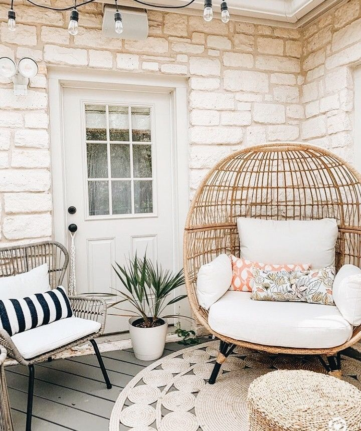 rattan chairs with white cushion, exposed white wall, wooden floor, rattan chair with white cushion, rattan ottoman, rattan rug