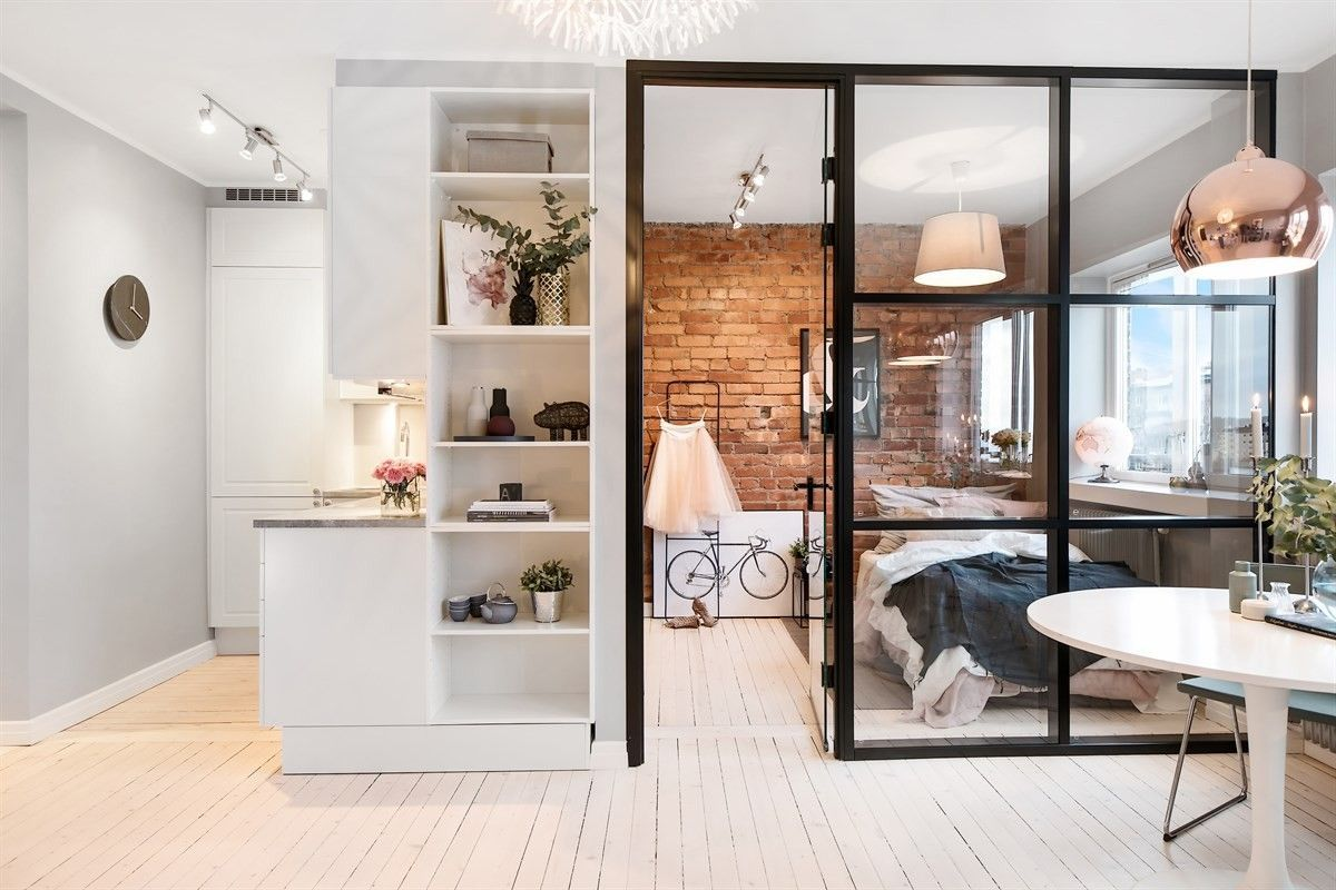 small apartment, wooden floor, grey wall, white shevels, bedroom with glass partition, white chandelier