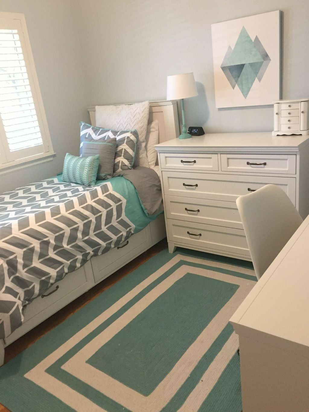 small bedroom, wooden floor, light green wall, white bed platform with drawers, white cabinet, green rug, white green table lamp, white table