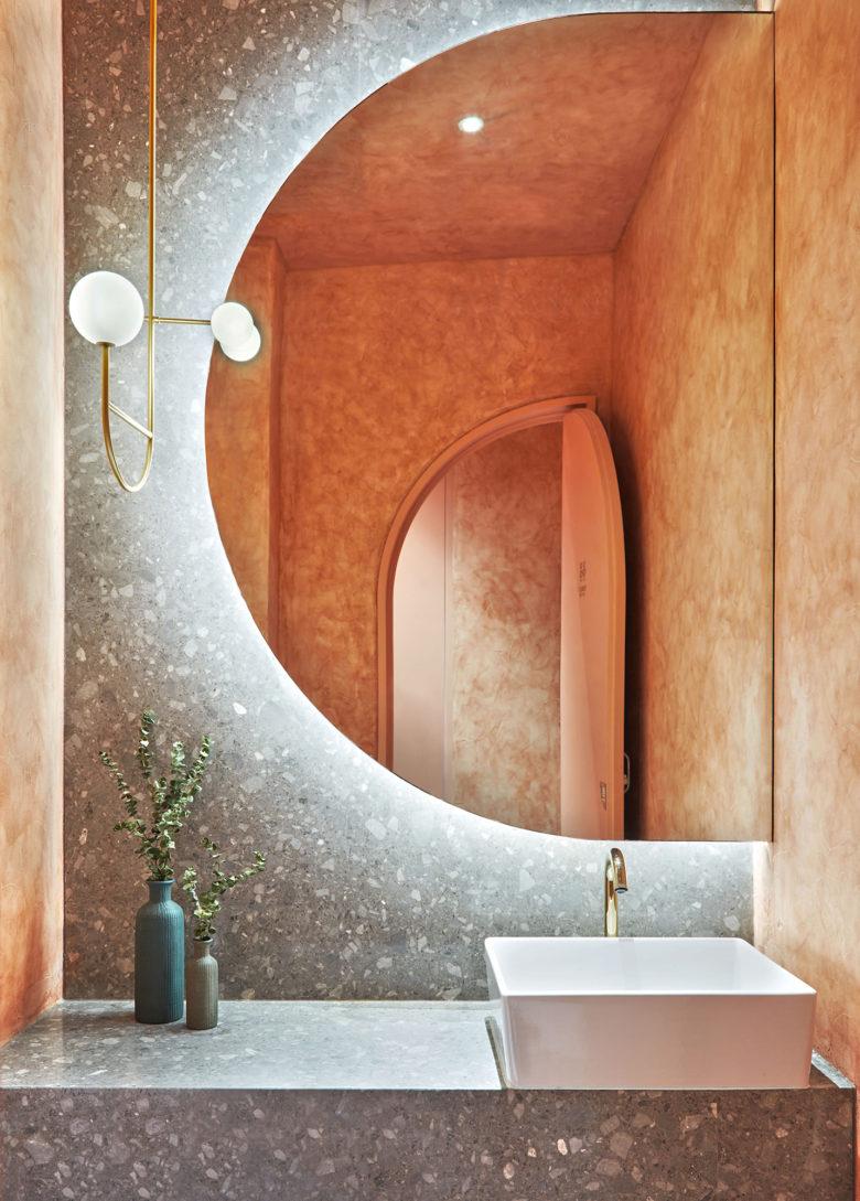 vanity, grey marble, white sink, half round mirror, golden pendant with white bulbs,