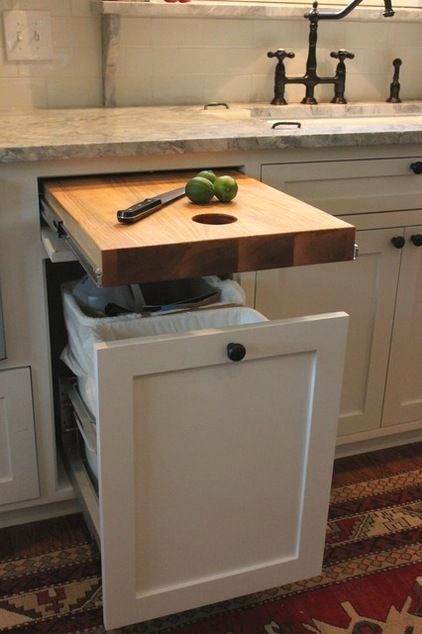 white kitchen cabinet, wooden cutting board inside the drawer, grey marble counter top
