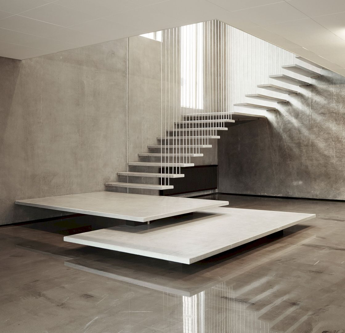 white staircase, white long fences from the ceiling, large platform