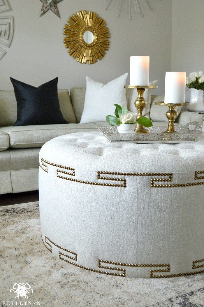 white tufted round ottoman, grey sofa, grey rug, white wall, clear tray