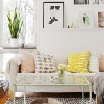 White Wall, White Sofa, Wooden Floor, Striped Rug, Coffee Table With Glass Top, Green Frame, White Floating Shelves