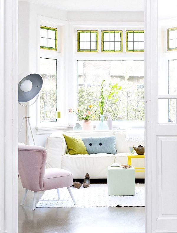 white wall, whtie sofa, seamless floor, white rug, pink chair, green ottoman