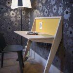 Wooden Table, Angled Legs, Black Chair, Yellow Board, Floor Lamp, Flower Wallpaper