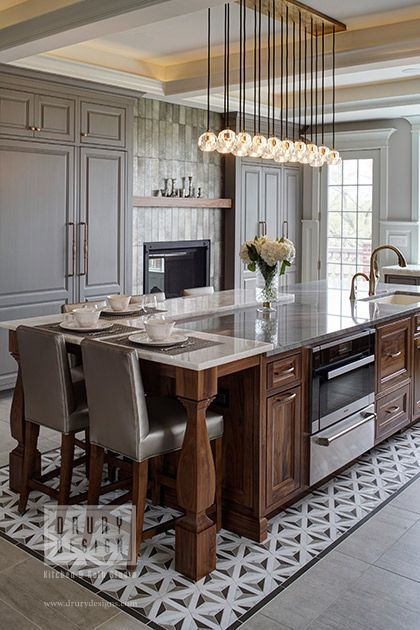 accent ceiling, white beams on the ceiling, bulbs pendants, grey wall, grey cabinet, dark wooden island with marble top, wooden chair with grey cushion