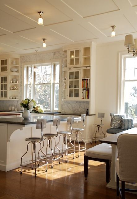 accent ceiling, white coffered ceiling, little ceiling lighting fixture, white wall, white island with black top, metal stools