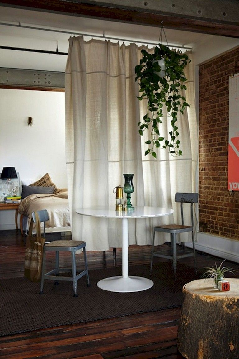 apartment, wooden floor, exposed brick wall, white round table, grey chairs, bed