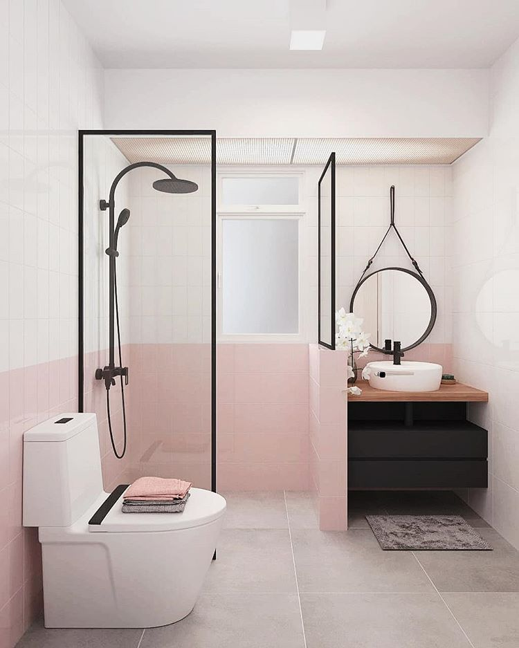 bathroom, brown floor, white and pink wall tiles, round mirror, black vanity, wooden vanity top, white round sink, white toilet