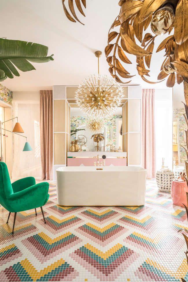 bathroom, colorful tiny floor tiles, brown wall tiles, white tub, green velvet chair, chandelier, orange green floor lamp,golden accessories