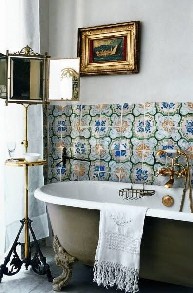 bathroom, grey floor, grey tub with white inside, white wall, patterned wall tiles, golden standing mirro