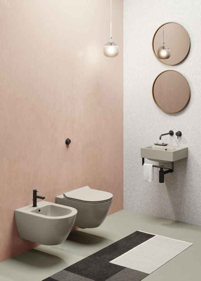 bathroom, grey seamless floor, pink wall, white wall, round mirrors, small floating sink, floating sink and toilet