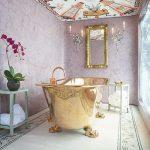 Bathroom, Pink Wall, Colorful Patterned Ceiling, Golden Framed Mirror, Golden Tub, White Patterned Rug, Sconces