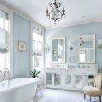 Bathroom, White Floor Tiles, Blue Wall, Chandelier, White Tub, White Cabinet, White Sconces, White Marble Counter Top, White Framed Mirrors