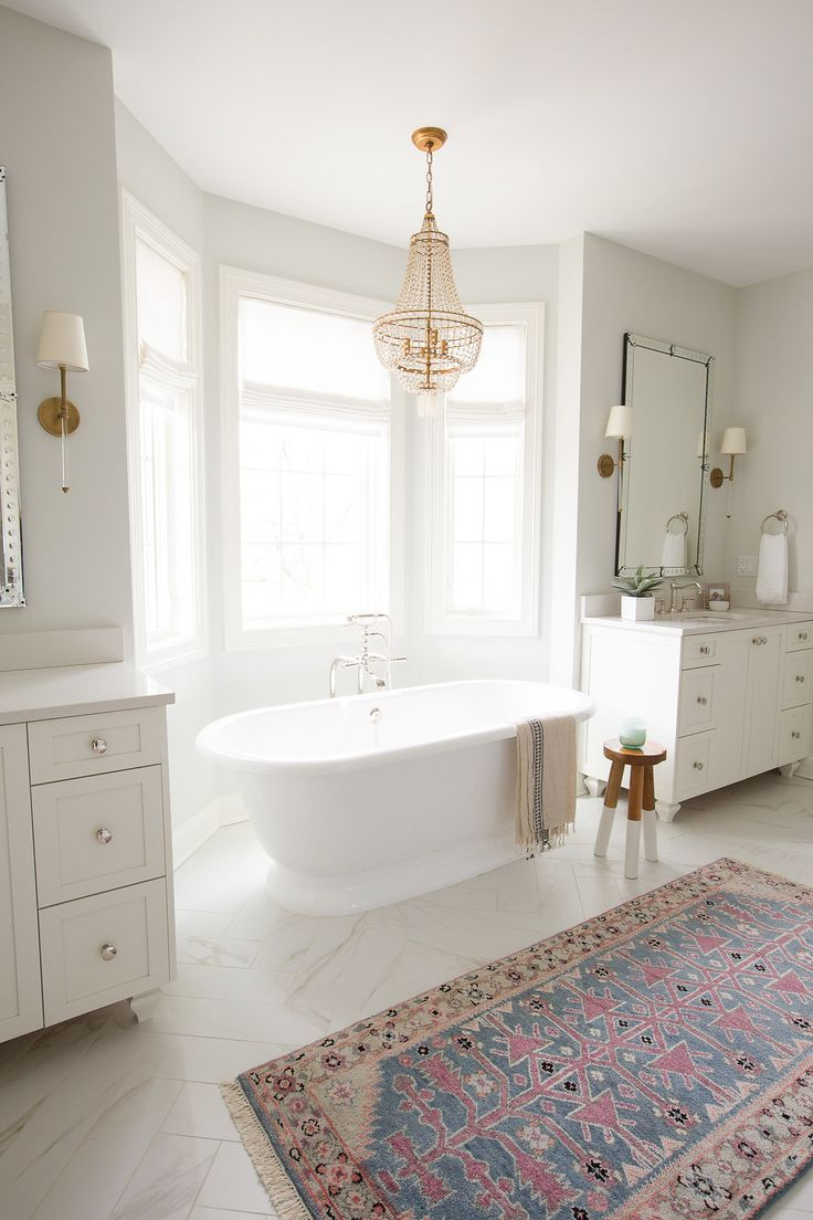 bathroom, white marble floor, patterned rug, white wall, white cabinet, mirror, chandelier, white sconces