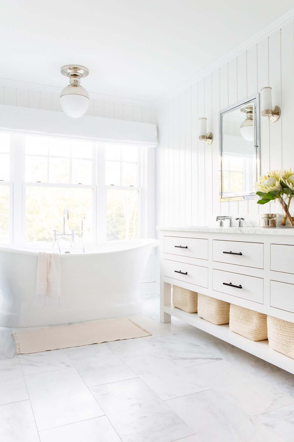 bathroom, white marble floor, white vertical shiplank, white lighting fixture, white wooden cabinet, white marble counter top, white sconces, mirror