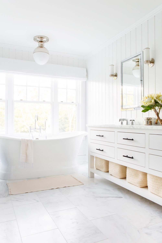 bathroom, white marble floor, white vertical shiplank, white lighting fixture, white wooden cabinet, white marble counter top, white sconces, mirror