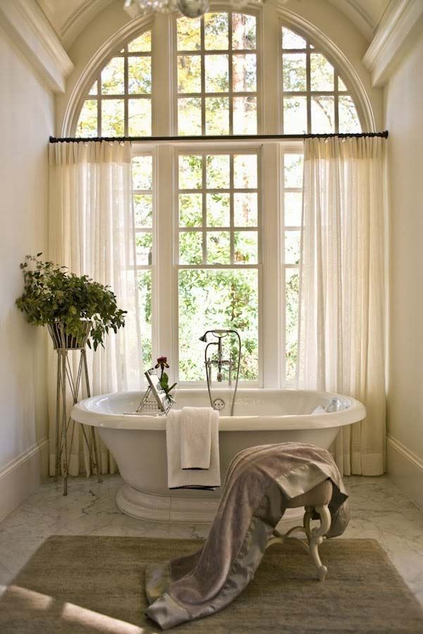 bathroom, white marble floor, white wall, white tub, white curtain, dome ceiling, half round window, chandelier
