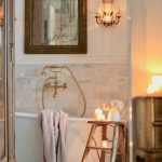 Bathroom, White Marble Floor, White Wooden Wall, White Tub With Golde Claw Foot, Sconce. Golden Faucet