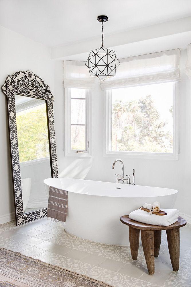 bathroom, white patterned floor, white wall, patterned framed mirror, white tub, wooden side table, patterned rug, white modern pendant