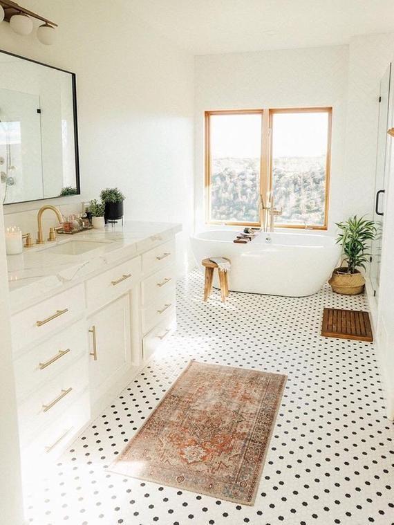 bathroom, white wall, white tub, wooden framed, white cabinet, white marble counter top, white small floor tiles, mirror