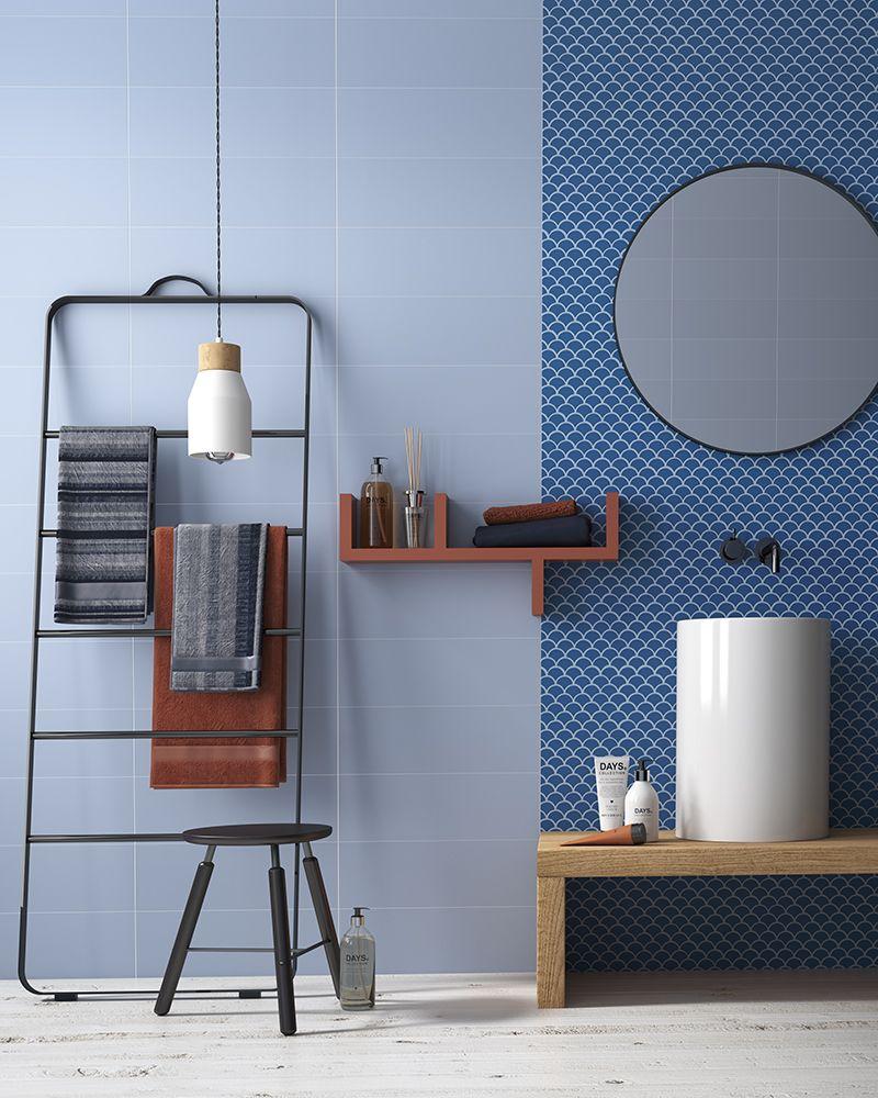 bathroom, wooden floor, blue wall tiles, blue accent tiles, white sink, wooden vanity, black rack, pendant, floating shelves, round mirror