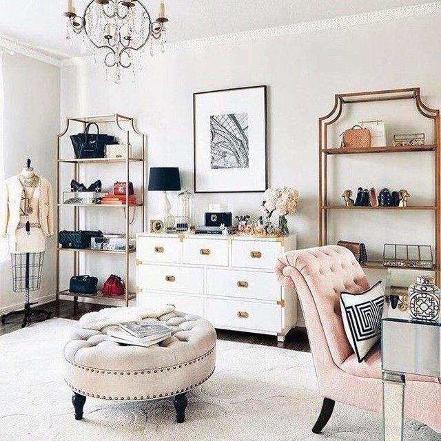 beauty room, dark wooden floor, brown tufted ottoman, pink tufted chair, white cabinet, golden shelves, chandelier