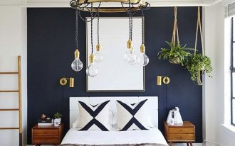 bedroom, concrete floor, bed headboard, blue accent wall, white wall, wooden bench, wooden rack, bulub pendant, hanging plants
