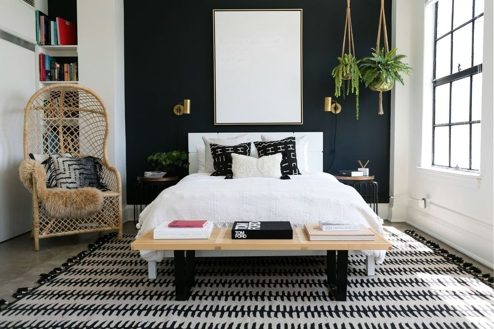 bedroom, concrete floor, dark blue accent wall, white wall, hanging plants, side table, rattan chair, indented shelves