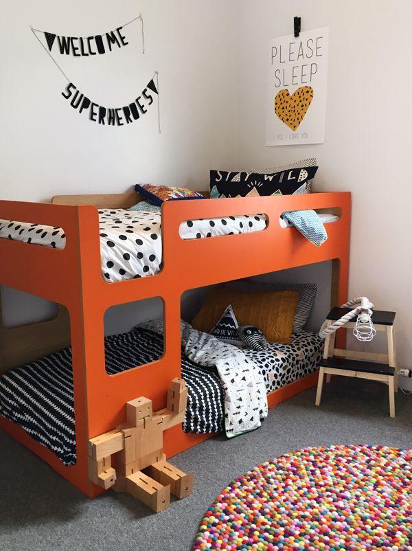 bedroom, grey floor, colorful round rug, orange bunk bed platform, white wall