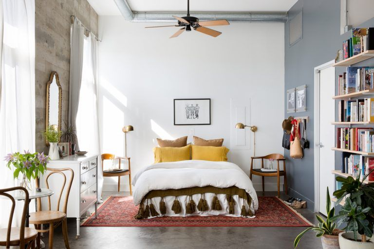 bedroom, grey floor, white wall, grey wall, white bedding, yellow pillow, ceiling fan, white cabinet, floating shelves, wooden chair, small round table