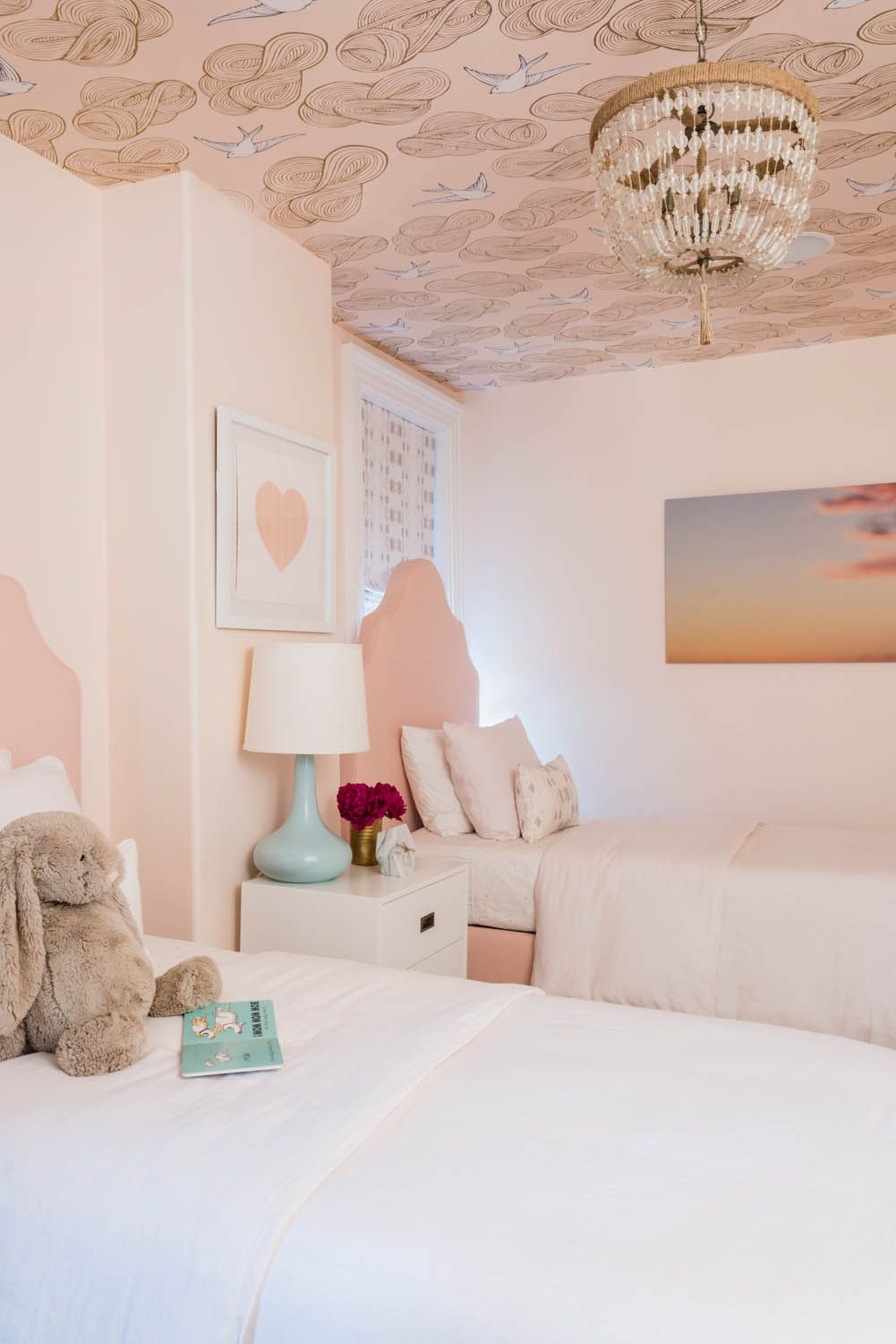 bedroom, off white wall, pink bed platform, white side cabinet, white blue table lamp, patterned ceiling, chandelier