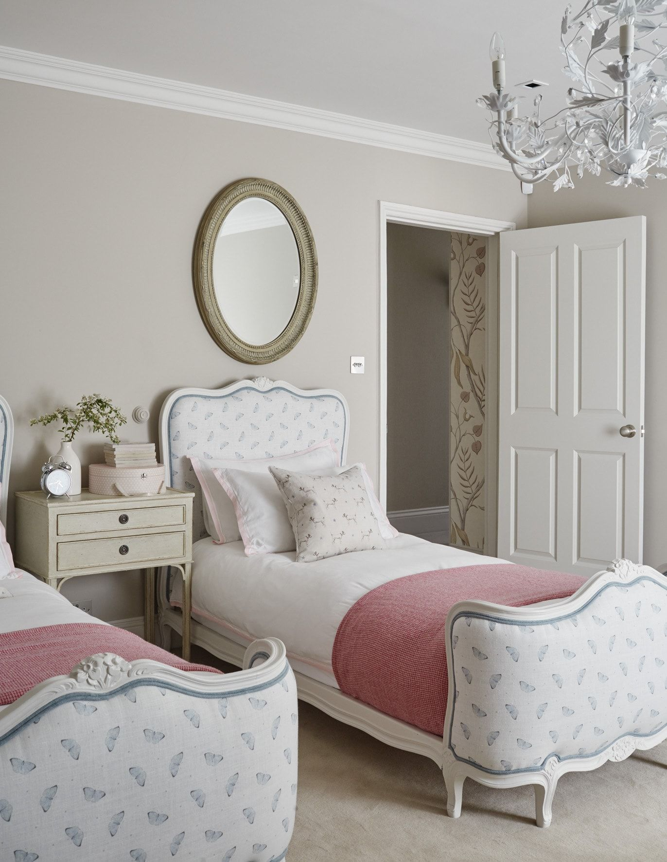 bedroom, white classi bed platform, cream wall, white chandelier, white side table with drawers