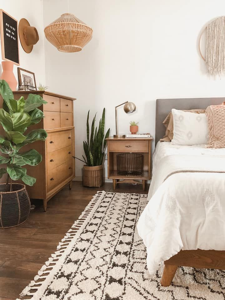 bedroom, wooden cabinet, white wall, bed with grey headboard, wooden side table, wooden floor, white patterned rug