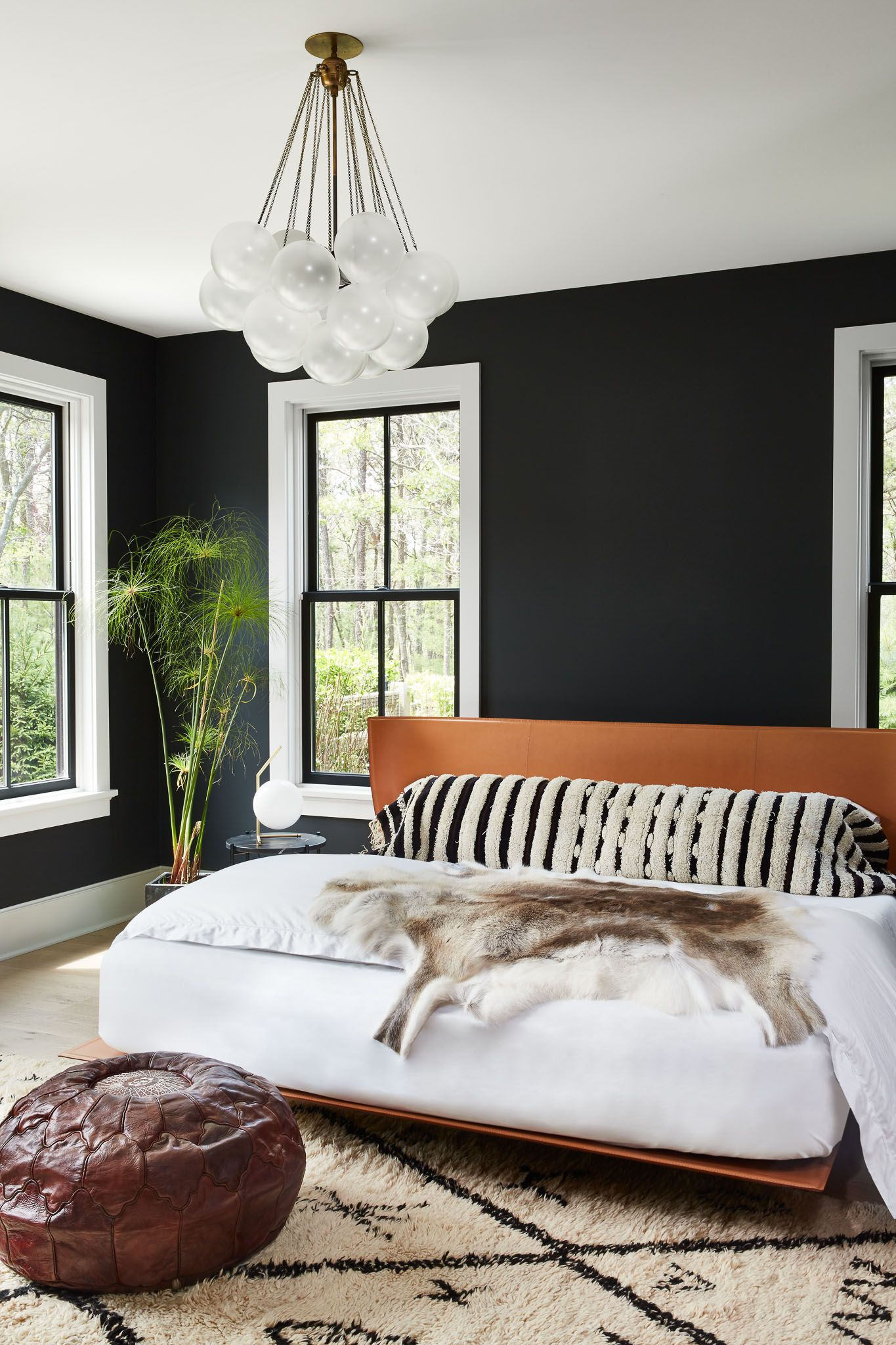 bedroom, wooden floor, balck wall, windows, smooth wooden bed platform, patterned rug, brown leather ottoman