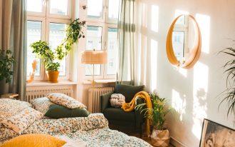 bedroom, wooden floor, white wall, flowery bedding, round mirror, dark chair, green curtain