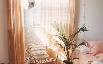 bedroom, wooden floor, white wall, orange curtain, wooden bed platform, rattan chair, plants on the floor