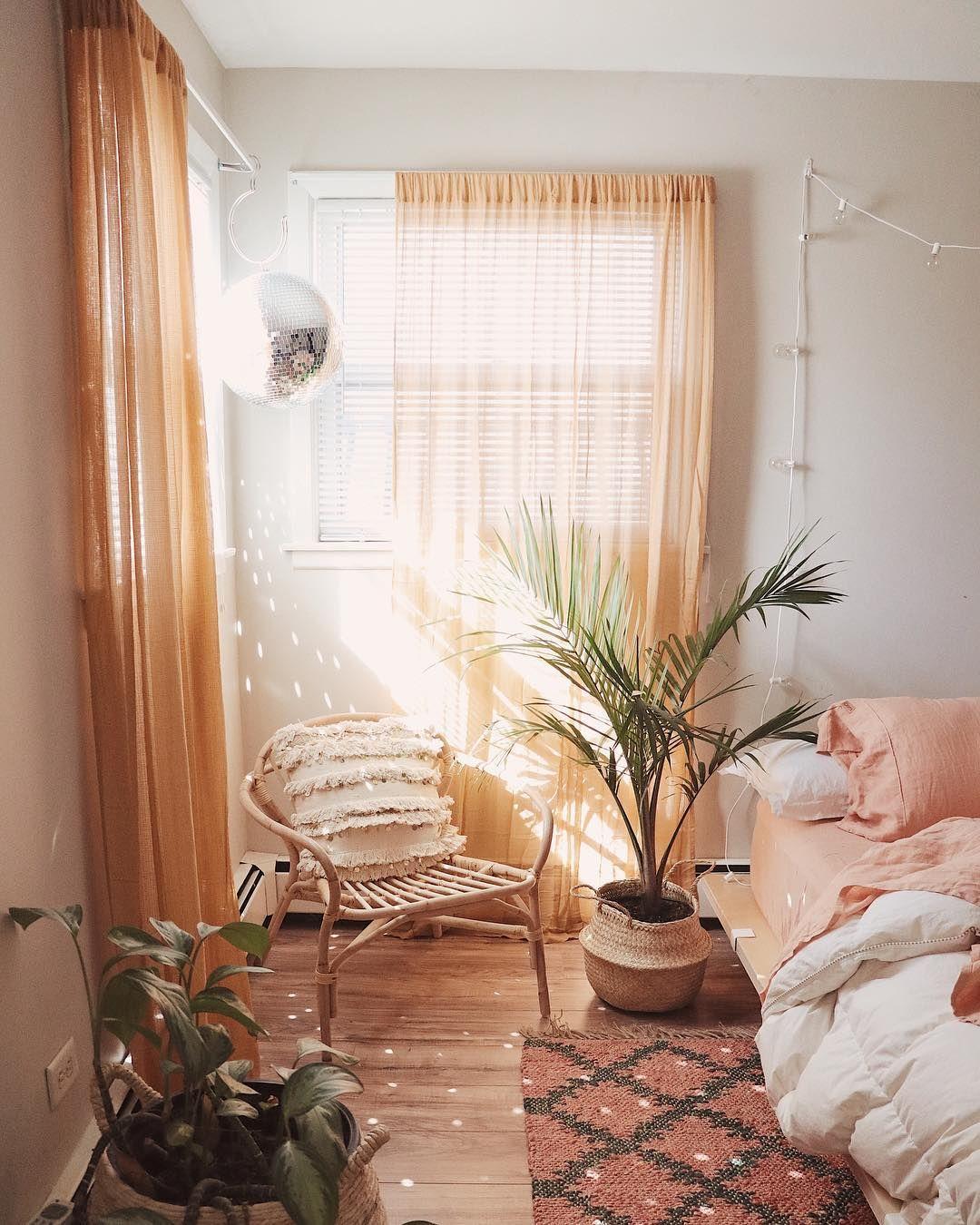 bedroom, wooden floor, white wall, orange curtain, wooden bed platform, rattan chair, plants on the floor
