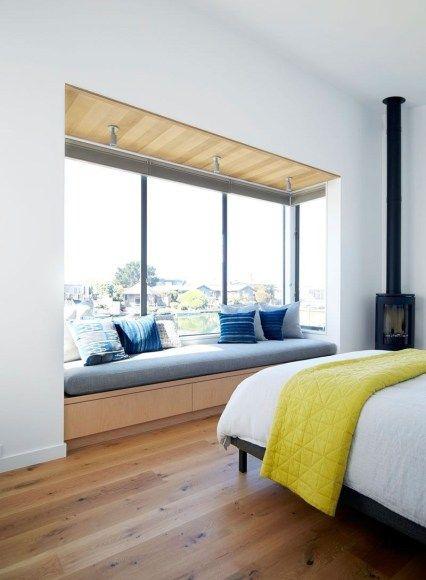 bedroom, wooden floor, wooden cabinet seat, blue cushion, blue pillows, black bed platform