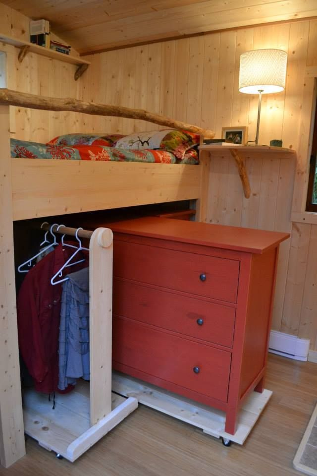 bedroom, wooden wall, wooden bunk bed, cabinet and clothes rack under, floating wooden shelves, white lamp