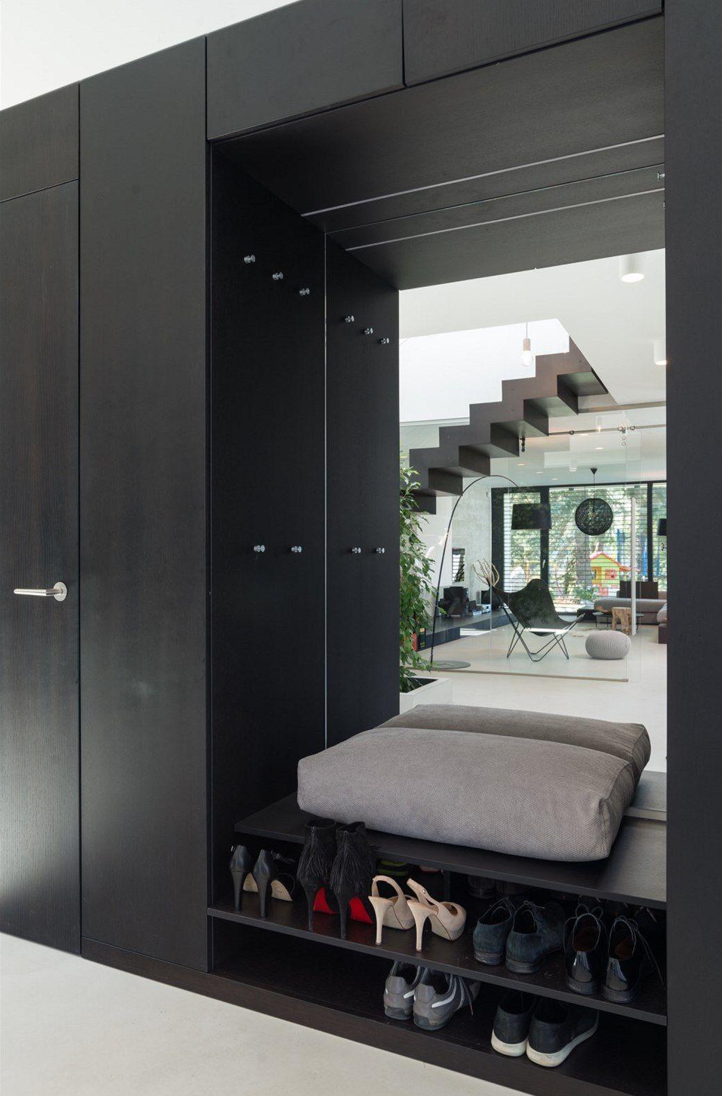 black entrance, black cupboard, black shelves, grey cushion, mirror