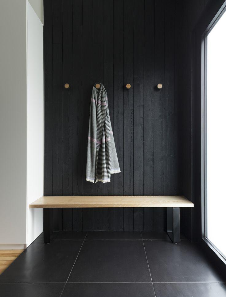 black entrance, black floor tiles, black wooden wall, wooden bench