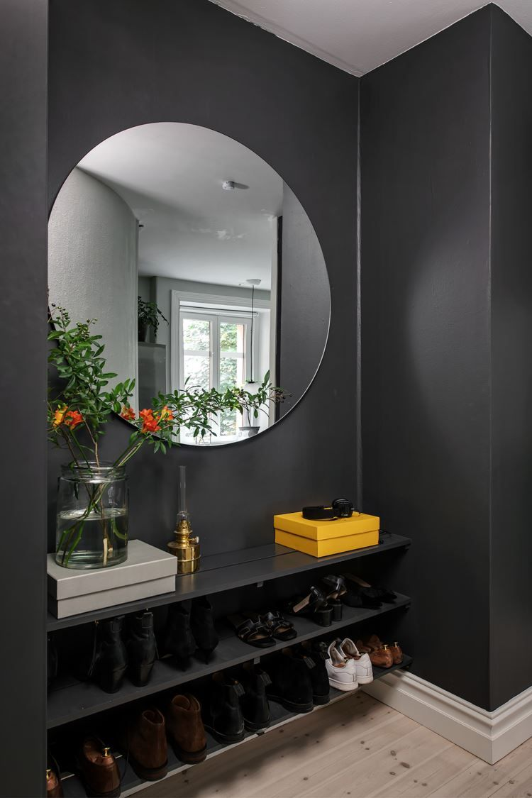 black entrance, black wall, black shelves, wooden floor, round mirror