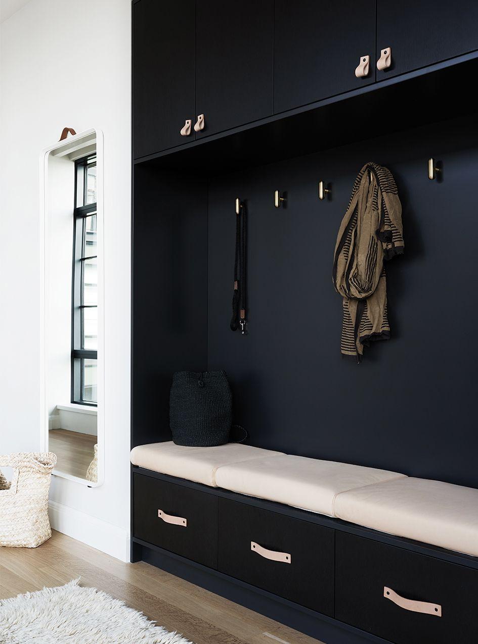 black entrance, white cushion, white wall, wooden floor, mirror